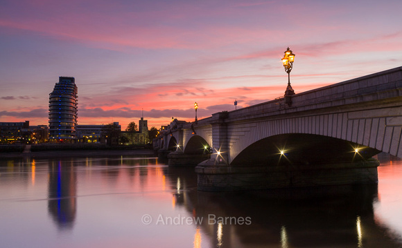 A dramatic winter sunset is reflected in the River Thames at Putney Bridge at dusk, viewed from the Fulham bank looking towards St. Mary's church and the Putney Wharf area