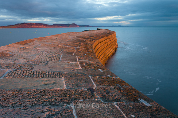 The old harbour wall of The Cobb at Lyme Regis glows as it catches the rays of the setting winter sun. In the distance are the cliffs of Golden Cap on the Jurassic Coast.