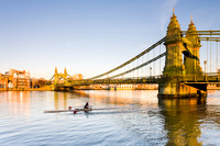 A sculler on the River Thames passes underneath the iron suspension bridge of Hammersmith Bridge, London, in the late afternoon sunshine.