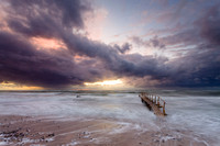 A small wooden bathing jetty stands in a storm-whipped sea under sunset clouds, at Smidstrup Strand, on the north coast of Zealand in Denmark.