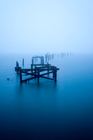 A long exposure blurs the waters around the remaining wooden posts of the old pier at Swanage in Dorset. The end of the pier recedes into the mist.