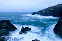 Trevose Head lighthouse in Cornwall, shown with stormy waves crashing against the rocks and cliffs below at dusk.