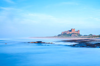 A long-exposure view of Bambrugh Castle and beach, lit by the setting sun in summer. Northumberland, July 2014