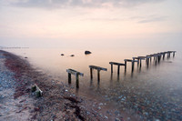 A small wooden bathing jetty stand in calm shallow waters at sunset, at Smidstrup Strand, on the north coast of Zealand in Denmark.