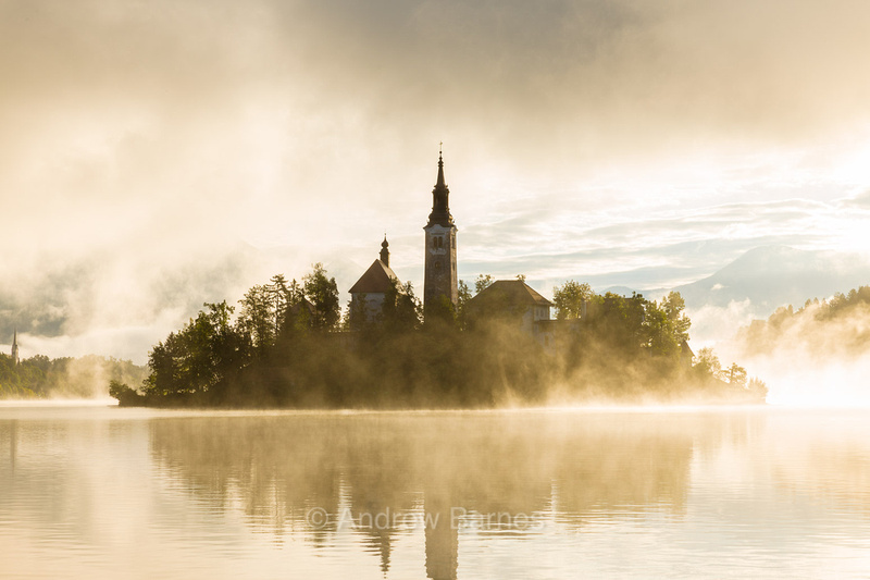 The Church of the Assumption on an island in the middle of Lake Bled, Slovenia, is shrouded in mist as the sun rises