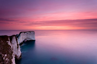The chalk cliffs of Old Harry Rocks at Studland, Dorset, next to a calm sea under a pink pre-dawn sky
